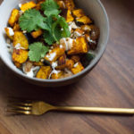 An easy weeknight vegetarian dinner or warm lunch recipe for a spicy curry roasted squash bowl with lemon yogurt and pickled golden raisins.